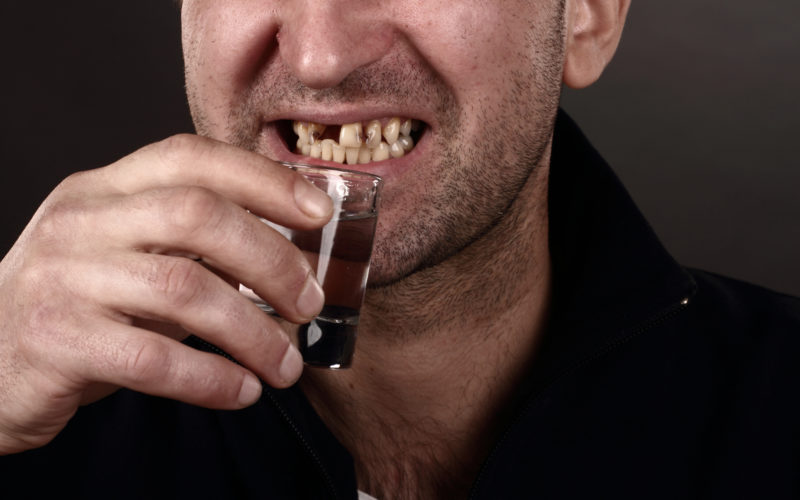 Man with Damaged teeth drinking alcohol
