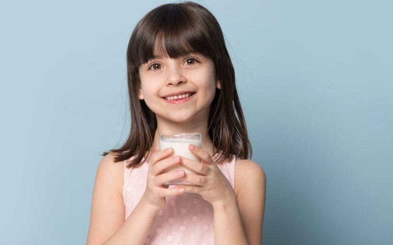 Child holding glass of milk