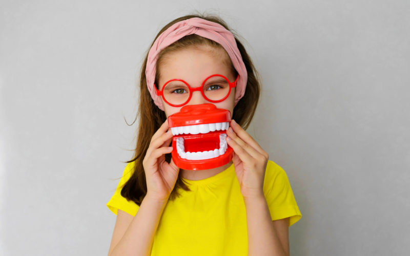 Smiling playful child with false teeth