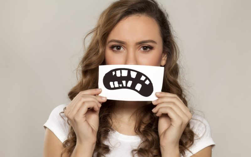 Woman holding frowning image of bad teeth